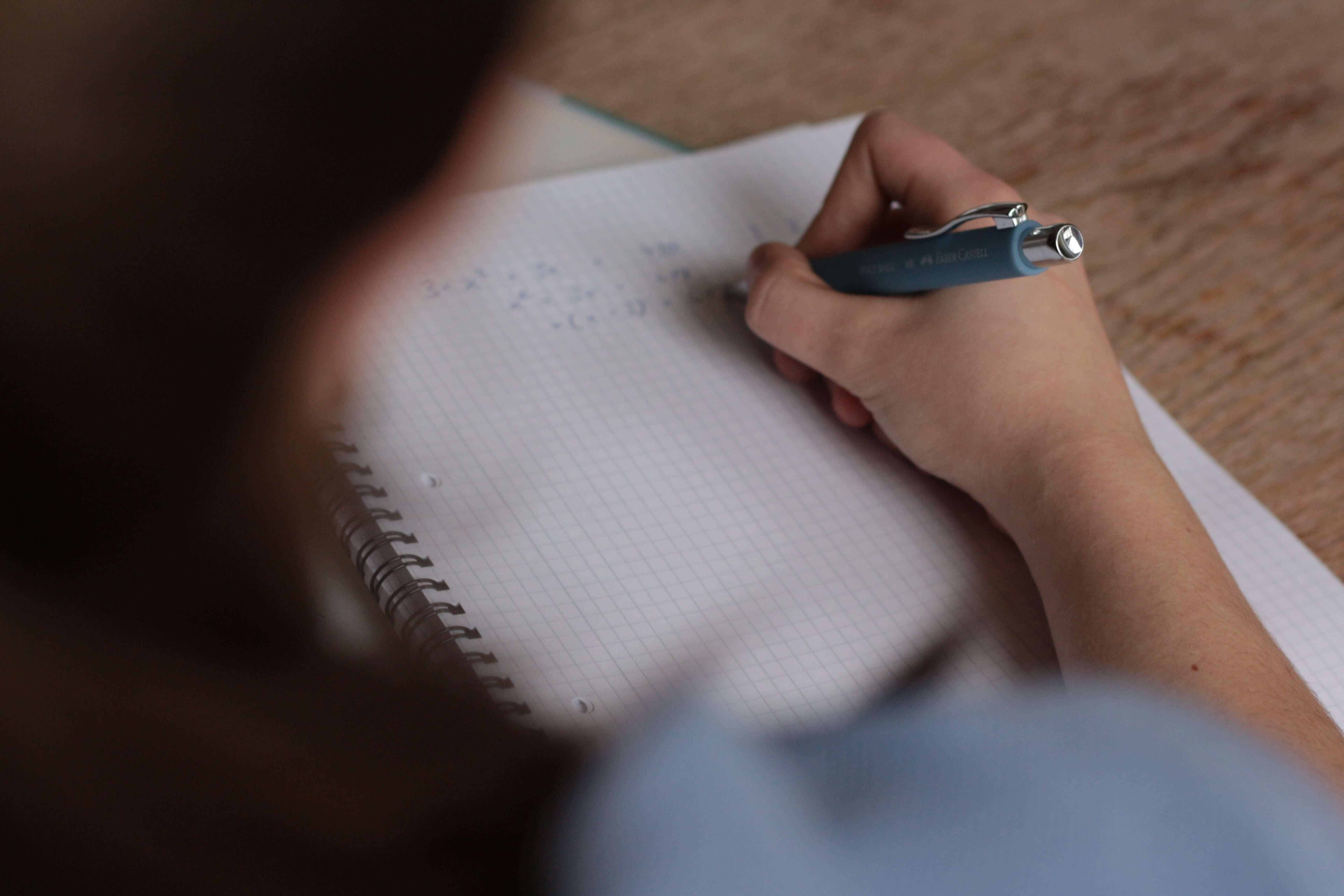 ученик на изпит пише в тетрадка