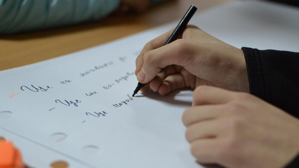 ръка пише на бял лист
